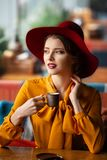 Portrait of sensual young girl. Wearing floppy hat and blouse with bow. Beautiful brunette woman in cafe holding cup of coffee royalty free stock photography