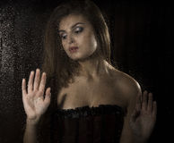 Portrait of a sensual young sexy woman wearing corset, touching her hair and posing behind transparent glass covered by Stock Photography