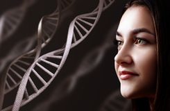 Portrait of sensual young woman among DNA chains. Over black background stock image