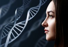 Portrait of sensual young woman among DNA chains. Over black background royalty free stock images