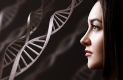 Portrait of sensual young woman among DNA chains. Over black background stock photos