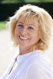 Portrait of serene mature woman in the summer park Stock Images