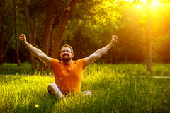 Portrait of serene meditating man with beard in a summer park. Portrait of serene meditating man with beard in a park at summer golden sunset natural background royalty free stock photography