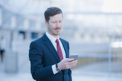 Business man looking at his phone. Portrait of a serene and quiet man wearing a dark blue business suit, he`s looking at his cellular telephone Royalty Free Stock Photos