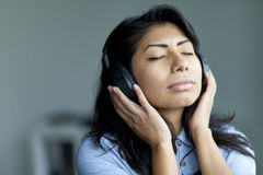 Portrait Of A Serene Spanish Woman Listening Music. At Home stock photography