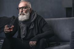 Serious retire tasting beverage on couch. Portrait of serene unshaven grandfather drinking alcohol while sitting on cozy sofa in apartment. Rest concept Royalty Free Stock Photography