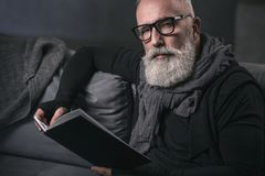 Serious retire male reading interesting book. Portrait of serene unshaven old man looking through volume while locating in comfortable couch at home. Leisure Stock Images
