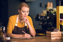 Serious female barista writing in clipboard. Portrait of serene worker filling information while situating at counter in comfortable cafe. Job concept Stock Photography