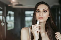 Calm attractive lady rouging the lips indoor royalty free stock photos