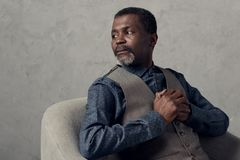Portrait of serious african american man. In waistcoat sitting in armchair royalty free stock image