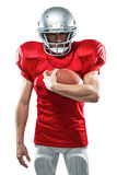 Portrait of serious American football player in red jersey holding ball. On white background Stock Images