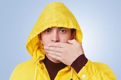 Portrait of serious attractive fashionable guy covers mouth with hands, tries not to tell friend`s secret, keep private informatio Stock Image