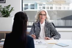 Confident serene senior woman listening to her worker stock photography