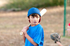 Portrait of serious baseball boy with wooden bat. Outdoor portrait of a young baseball kid in blue shirt looking serious and sideways holding a wooden bat Stock Image
