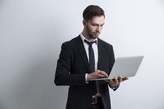 Portrait of a serious bearded young businessman standing near a white wall and working with his laptop. Stock Photos