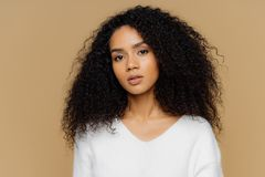 Portrait of serious beautiful dark skinned female with frizzy black hair, has minimal makeup, looks calmly at camera, wears white. Jumper, stands against brown stock image