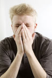 Portrait of serious blond man closing his eyes by Stock Photos