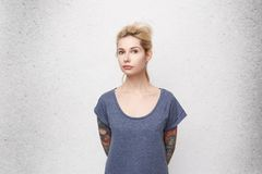 Portrait of serious blonde girl looking directly in camera cross her hands back. Wearing casual blue t-shirt. Tattooes. Pierced nose. Isolated over studio stock photography