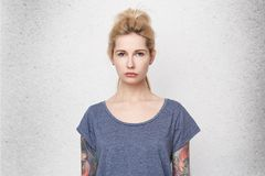 Portrait of serious blonde girl wearing blue t-shirt, tattoed arms and pierced nose sad and confused. She lost her boyfriend. Isolated over white studio wall stock images