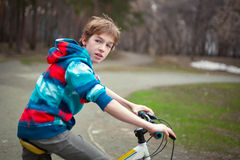 Portrait of serious boy with bicycle in park Stock Photography