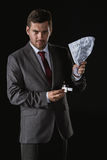 Portrait of serious businessman holding contract and cigarette lighter Stock Photos