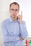 Portrait of serious businessman at office showing his index fing. Portrait of businessman in shirt at office showing his index finger Stock Images