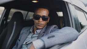 Portrait of serious businessman in sunglasses sitting inside car and looking into camera outdoors. Portrait of serious african american businessman in sunglasses Stock Photo