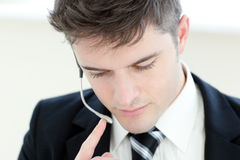 Portrait of a serious businessman using earpiece Royalty Free Stock Photos