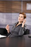 Portrait of serious businesswoman on phone. Portrait of serious businesswoman focusing on mobile phone call at desk in office Royalty Free Stock Images