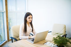 Portrait of a serious businesswoman using laptop in modern office Stock Images