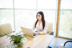 Portrait of a serious businesswoman using laptop in modern office Royalty Free Stock Photos