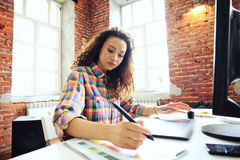 Portrait of a serious businesswoman using laptop in office. Beautiful hipster woman taking notes at modern office. Stock Photos
