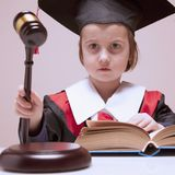 Portrait of serious child girl judge lawyer doubts the decisio royalty free stock images