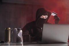 Serene hacker pilfering digital cash stock photography