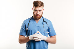 Portrait of a serious concentrated male medical doctor or nurse. Wearing surgical gloves and looking at camera isolated on white background Royalty Free Stock Photos