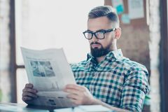 Portrait of serious confident concentrated young stylish guy wearing glasses and checkered shirt, he is reading stock images