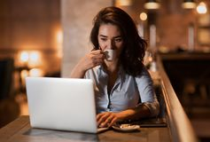 Portrait of serious elegant businesswoman sitting at modern restaurant working on her laptop and drinking coffee. Portrait of serious handsome elegant caucasian Royalty Free Stock Images