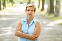 Portrait of a serious emotional elderly woman in the park. Emotion, age and people concept - portrait of a beautiful senior woman in the park looking serious and Royalty Free Stock Photography