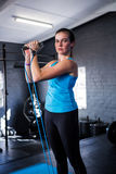 Portrait of serious female athlete stretching resistance band Royalty Free Stock Image