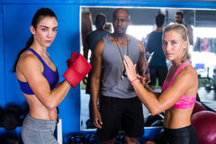 Portrait of serious female boxers by coach Stock Image