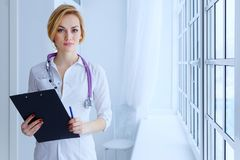 Portrait of serious female doctor with clipboard. Stock Photos