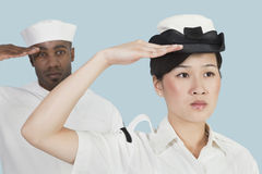 Portrait of serious female US Navy officer and male sailor saluting over light blue background Stock Photo