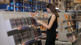 Portrait of serious girl in library or book store or supermarket looking for a book, brunette woman in shop. stock video footage