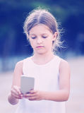Portrait of serious girl  looking at mobile phone Royalty Free Stock Photos