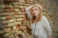 Portrait of serious girl near a brick wall, Royalty Free Stock Photo