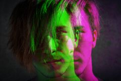 Portrait of a serious guy with disheveled hair on a gray concrete wall background. Digital signal glitch effect rgb shift, slice stock photo