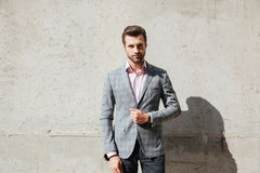 Portrait of a serious handsome man in a jacket standing. And looking at camera infront of a wall Stock Images