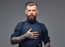 Portrait of a serious handsome old-fashioned hipster in shirt and suspenders. Stock Photo