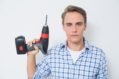 Portrait of a serious handsome young handyman holding drill Royalty Free Stock Photo