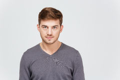 Portrait of serious handsome young man in grey pullover. Over white background Royalty Free Stock Image
